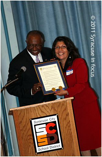 Council President Van Robinson presents a city proclamation to on-air personality Fanny Villarreal during the Hispanic Heritage Month yesterday at Delaware Academy.