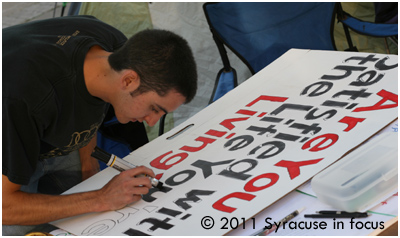 Matt Figueroa, who first visited Occupy Syracuse on Tusday, works on a sign at the site