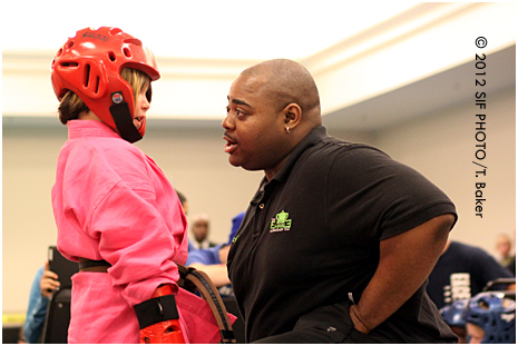 Head judge Ritchie Everage gives a pep talk to a competitor at the New York State Martial Arts Showcase on Friday night.