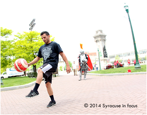 Syracuse Silver Knights midfielder Anthony Meola does some fancy footwork (under the watchful eye of the team mascot) during yesterday's Cuse Give Mob event downtown.