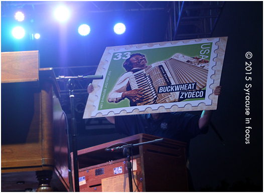 Syracuse Jazz Fest Producer Frank Malfitano holds up a sign to get the crowd to cheer on Buckwheat Zydeco to do one more encore last night.