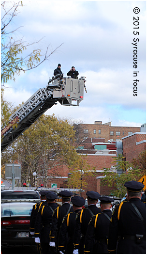 A photographer got a better vantage point to photograph members of the Syracuse Police Department along the Connective Corrridor on Friday.