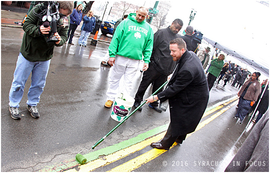City of Syracuse Director of Policy & Innovation Andrew Maxwell paints a stripe along S. Salina Street ahead of the St. Patrick's Parade, which will be held later today.