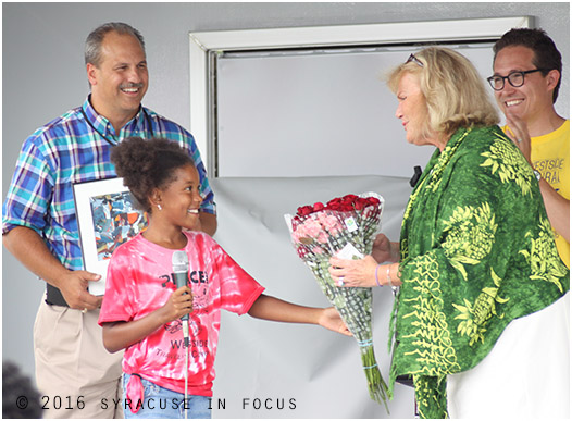 Marilyn Higgins was given an award today during the Near Westside Initiative's Multicultural Block Party today. She  was also serenaded for her birthday. She accepted a bouquet by a student during ceremony and was joined on stage by  Near Westside executives Robert Daino  (left) and Marteen Jacobs.